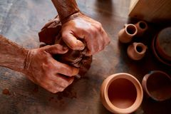 Hands of male potter molding a clay in pottery workshop, close-up, selective focus. Creative work process. Craftsman preparation for making a masterpiece at Stock Image