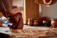 Hands of male potter molding a clay in pottery workshop, close-up, selective focus. Creative work process. Craftsman preparation for making a masterpiece at Royalty Free Stock Photos
