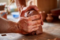 Hands of male potter molding a clay in pottery workshop, close-up, selective focus. Creative work process. Craftsman preparation for making a masterpiece at Royalty Free Stock Photography