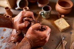 Hands of male potter molding a clay in pottery workshop, close-up, selective focus. Creative work process. Craftsman preparation for making a masterpiece at Stock Photos