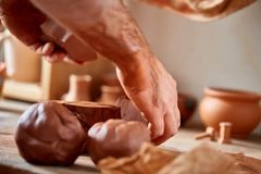 Hands of male potter molding a clay in pottery workshop, close-up, selective focus. Creative work process. Craftsman preparation for making a masterpiece at Stock Photography