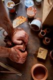 Hands of male potter molding a clay in pottery workshop, close-up, selective focus. Creative work process. Craftsman preparation for making a masterpiece at Royalty Free Stock Image