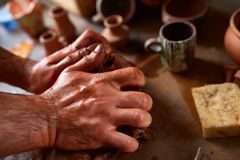 Hands of male potter molding a clay in pottery workshop, close-up, selective focus. Creative work process. Craftsman preparation for making a masterpiece at Stock Images