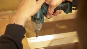 Hands of male screwing the bolt using electric screwdriver. Close up stock video footage