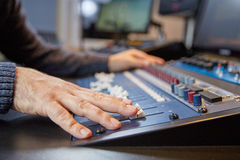 Hands of a man on adjusting a production console Stock Photos