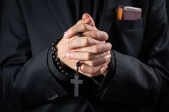 Christian person praying, low key image. Hands of a man in black suit or a priest portraying a preach royalty free stock images