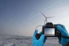 Hands man with blue gloves take picture of wind turbine on winter season Royalty Free Stock Photo