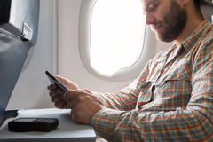 Hands of man browsing gadget in aircraft stock image