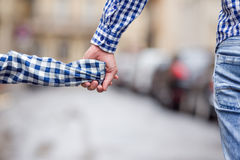 Hands of man and child holding together on street Stock Photo