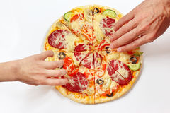 Hands of a man and a child are taking pieces of flavored pizza Stock Images