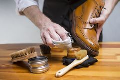 Hands of man cleaning premium derby boots with variety of brushes Stock Photography
