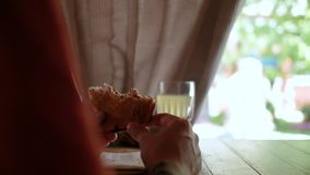 Hands of a man close up holding a sandwich in a cafe near the street. 4k. 4k video stock footage