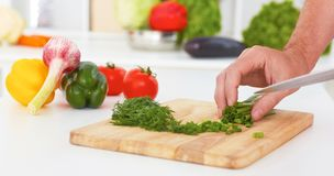 Hands of man is cooking vegetable salad in the kitchen closeup. stock photos