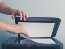 Hands of a man copying a piece of paper. The hands of a young man is placeing a piece of paper on a flatbed scanner in preperation for copying it royalty free stock photography