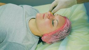 Hands of the man of the cosmetician in gloves remove from the face of the woman collagen pads under eyes. Close-up stock footage
