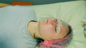 Hands of the man of the cosmetician put a liquid cosmetic mask on the woman`s face with a brush. Close-up stock footage
