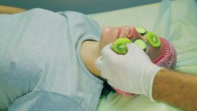 Hands of the man of the cosmetician remove from the face of the woman a mask from slices of a kiwi and a cucumber. Close-up stock video footage