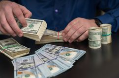 Hands of a man counting wads of dollar banknotes stock photo