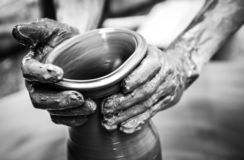 Hands of a man creating pottery on wheel, vintage style royalty free stock photography
