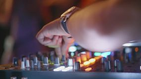 Closeup DJ hands mixes music at the party. Hands of man DJ play music on mixing console stock footage