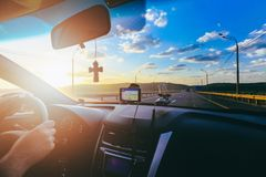 Hands of driver on steering wheel of car with orthodox cross and car navigator on the windscreen during driving on Stock Photos