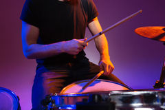 Hands of man drummer sitting and playing drums with drumsticks Royalty Free Stock Photography