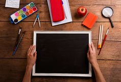 Hands of man with empty picture. Various school supplies. Stock Images