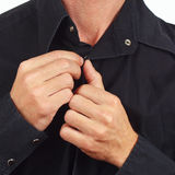 Hands a man fastened the buttons on the black shirt closeup Stock Image