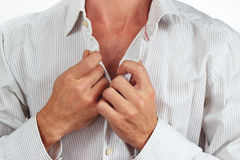 Hands a man fastened the buttons on the bright shirt closeup Royalty Free Stock Photography