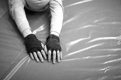 Hands of a man in fingerless gloves doing streching exercises Stock Photos