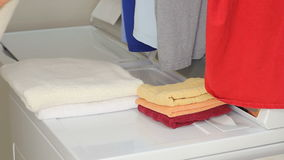 Hands of a Man Folding Laundry. Arms and hands of a male come in from the left wearing light clothes, folding a towel onto two other towels on top of a dryer in stock footage