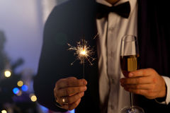 Hands of man holding Bengal light at the party. Sparkler - New Year`s Eve. Party, holidays, nightlife and people concept Royalty Free Stock Photography