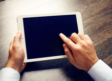 Hands of a man holding blank tablet device over workspace table. Hands of a man holding blank tablet device over a wooden workspace table Stock Photo
