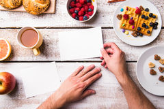 Hands of man holding empty greeting card. Breakfast meal. Stock Photo