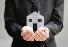 The hands of a man holding a house - insurance and protection concept Royalty Free Stock Photos
