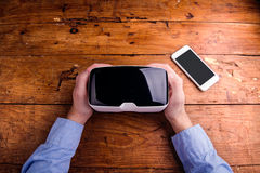Hands of man holding virtual reality goggles and smartphone Royalty Free Stock Photos