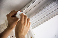 Hands of man installing curtains over window Royalty Free Stock Image