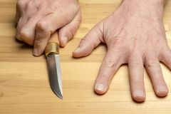 Hands of a man with a knife on a wooden table royalty free stock photo