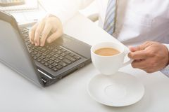 Hands of man on laptop with coffee and working on laptop. Hands of man on laptop and holding coffee cup and working on laptop Stock Photography