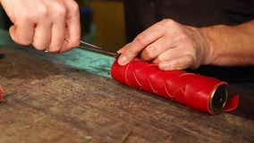 Master is fixing edge of leather strip on a red casing for kaleidoscope tube. Hands of man is locking border of leather case, using scissors. Craftsman is stock footage