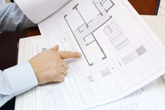 Hands of man looking drawings of apartment. Hands of man wearing white shirt and looking drawings of apartment in office of realtor stock photography