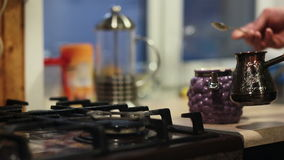 Hands of a man making coffee in a coffee pot with a long handle. He takes a teaspoon, puts some coffee into the coffee pot stock footage