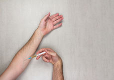 Hands of man making himself an injection of disposable medical syringe on gray background Stock Photography