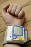The hands of an man measuring blood pressure with a wrist meter. Prevention of heart attack and stroke Royalty Free Stock Photography
