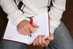 Hands of a man with a pen and an open notepad. The hands of a man with a pen and an open notepad Stock Image