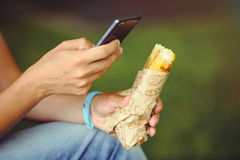 Hands of a man with a phone and street food, royalty free stock photos