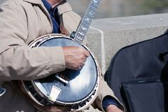 Hands of the man playing the banjo. Old man man playing the banjo on the bridge Royalty Free Stock Photography