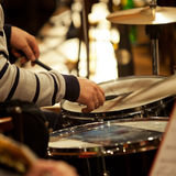 Hands of a man playing a drum set Stock Image