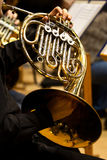 Hands of the man playing the French horn Royalty Free Stock Photos