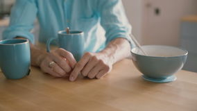 Hands of a man playing with his wedding ring at the kitchen table. Slow motion stock video
